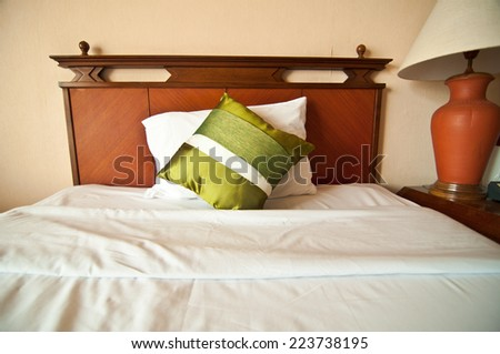 Room setting with bed and  silk pillows - stock photo