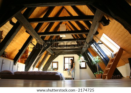 room under the roof, with dark wooden beams - stock photo
