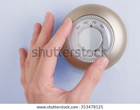 Room wall temperature thermostat turn  dial to set - stock photo