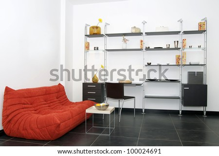 room with a sofa and a modern wardrobe for books and articles - stock photo