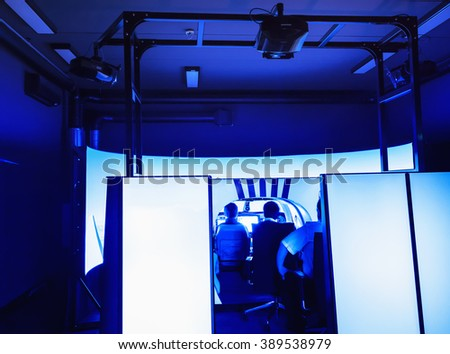 Room with an installed flight simulator for small private airplanes, blue colored. General view of the whole cabin. - stock photo