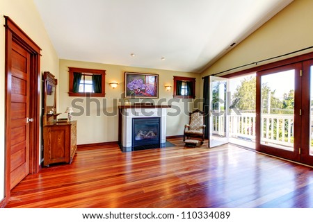 Room with beautiful chery hardwood floor and fireplace with open doors to the balcony. - stock photo