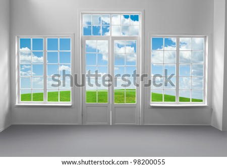 Room with large windows and green grass and blue sky behind (includes clipping path) - stock photo