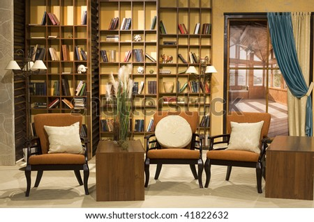 room with leather armchairs and bookshelf - stock photo