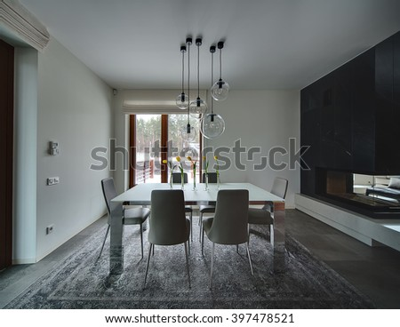 Room with light walls. On the floor there are gray tiles and a gray carpet. On the carpet stands table with frosted glass top and chromed carcass. On the table stand 5 glass vases with yellow tulips - stock photo