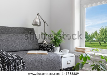 Room with modern decor and beautiful view over green garden. - stock photo