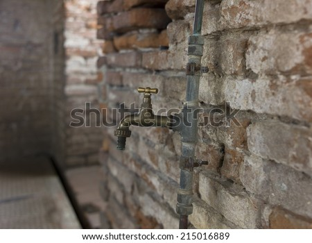 Room with old brick wall and copper water tap - stock photo