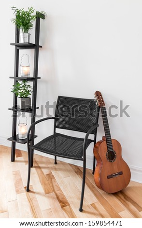 Room with simple black furniture, plants and classical guitar. - stock photo
