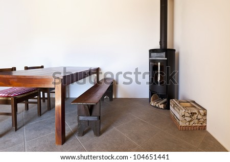 room with table and wood stove, rural home interior - stock photo