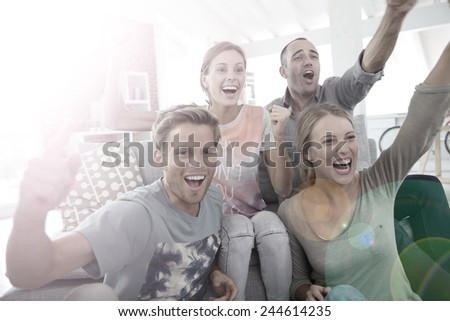 Roommates in apartment watching football game - stock photo