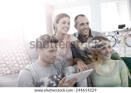Roommates in apartment watching tv - stock photo