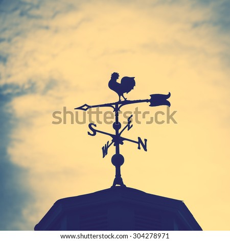 Rooster weather vane on a rooftop with an arrow and North-South pointer to show the direction of the wind against a hazy blue sky, vintage style - stock photo