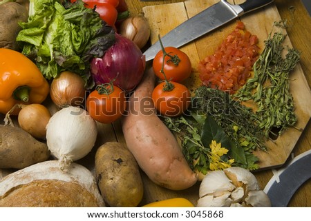 Root vegetables and herbs with a chopping board - stock photo