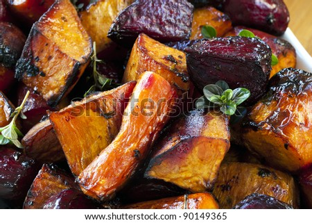 Root vegetables roasted with balsamic and thyme.  Includes beetroot, carrots, and sweet potato. - stock photo
