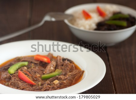 ropa vieja, a Cuban meal, on a plate with a black beans and rice  - stock photo