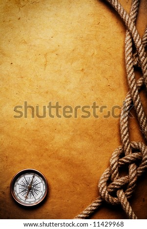 Rope and compass on the old paper background - stock photo