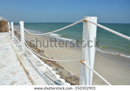 Rope and Wood Fence beside the beach - stock photo