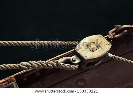 Rope boat vintage wooden pulley on old vessel - stock photo