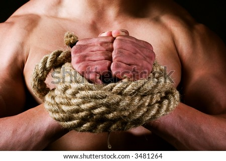 rope-bounded hands of young male athlete. Concept for freedom, struggle etc.
