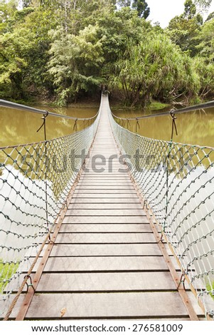 Rope bridge across a river in a jungle - stock photo