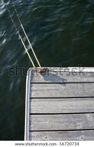 Rope cleated to dock - stock photo