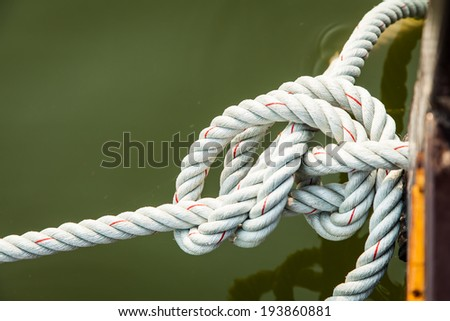 Rope for mooring a vessel is adhered to a pier  - stock photo
