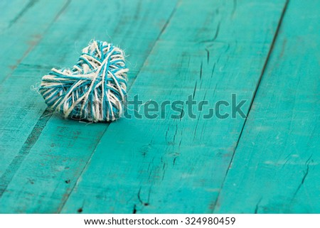 Rope heart on antique teal blue rustic wood background - stock photo