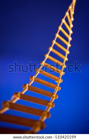 Rope ladder for climbing to top on blue background