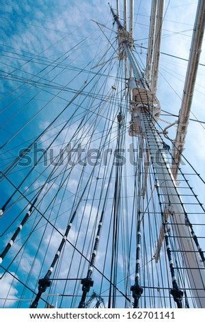 rope ladder to the main mast of the ship on blue sky background - stock photo