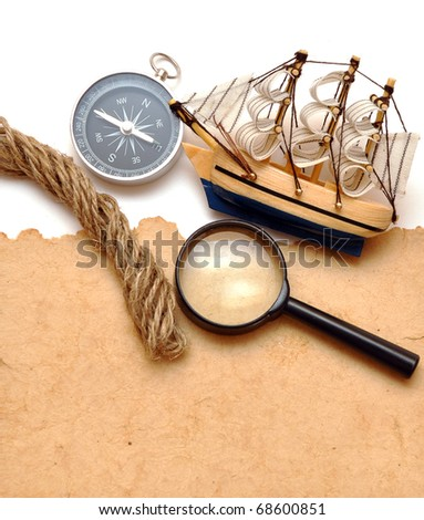 rope, magnifying glass, compass and model classic boat on old paper