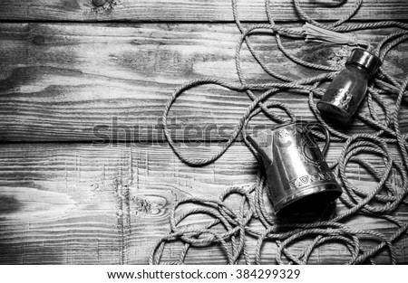 Rope, spices and metal utensils on old wooden burned table or board for background. Toned.