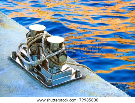 Rope tied in a knot on a bollard. Mooring rope wrapped around  the cleat on sea background. Metallic capstan in harbor for the mooring of yachts and boats. - stock photo