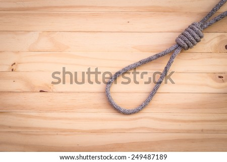 Rope with knotted on wooden background - stock photo