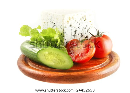roquefort and vegetables on wooden plate over white