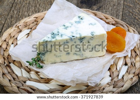 Roquefort cheese with thyme and dry apricot on the wood background - stock photo