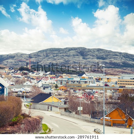 Rorvik, Norwegian town with colorful wooden houses on rocky hills under bright cloudy sky - stock photo