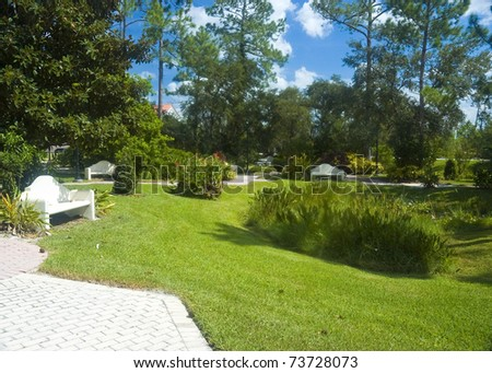 Rosary bead shaped paver sidewalk through a garden with concrete benches - stock photo