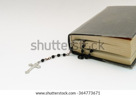 rosary beads in bible book on white background - stock photo