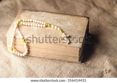Rosary beads on a vintage old books,horizontal photo - stock photo
