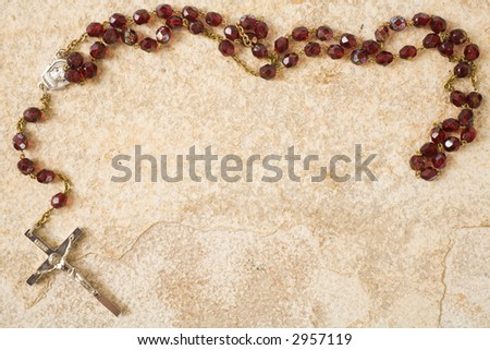 Rosary beads on stone with copy space - stock photo