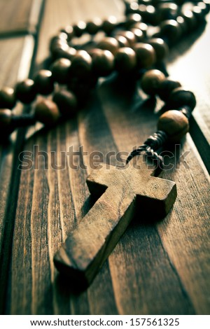 rosary beads on wooden table - stock photo