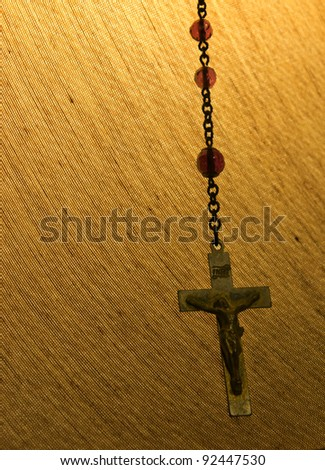 Rosary Chain hanging from a lamp shade.