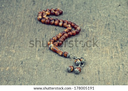Rosary laying on a grungy wooden background with retro filter effect  - stock photo