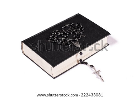 Rosary on Holy Bible isolated on white - stock photo