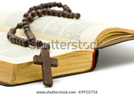 Rosary with holy bible over white background