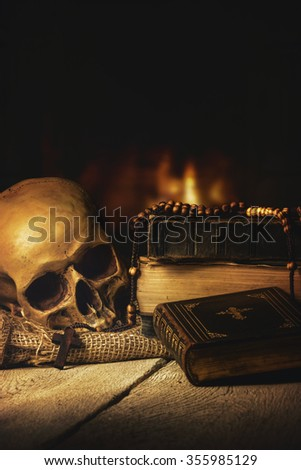 Rosary with Skull and Bible in front of a fireplace - stock photo