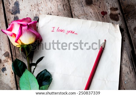 "Rose and a note with the text ""I love you"" on a wooden background. - stock photo"