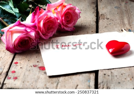 "Rose and a note with the text ""I love you"" on a wooden background.Ceramic red heart. - stock photo"
