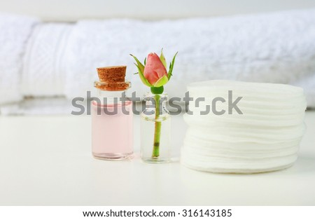 Rose attar cleaning tonic water fresh flower white cotton pads and towel, empty space, soft focus, bathroom daily care - stock photo
