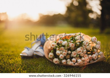 rose bouquet on green grass and women shoes - stock photo